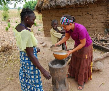 Shannon getting to help sift millet with one of the women in the bush